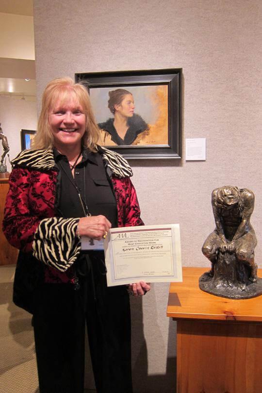 Karen holding AWA 'Most Evocative' Award with her Spirit Warrior Sculpture